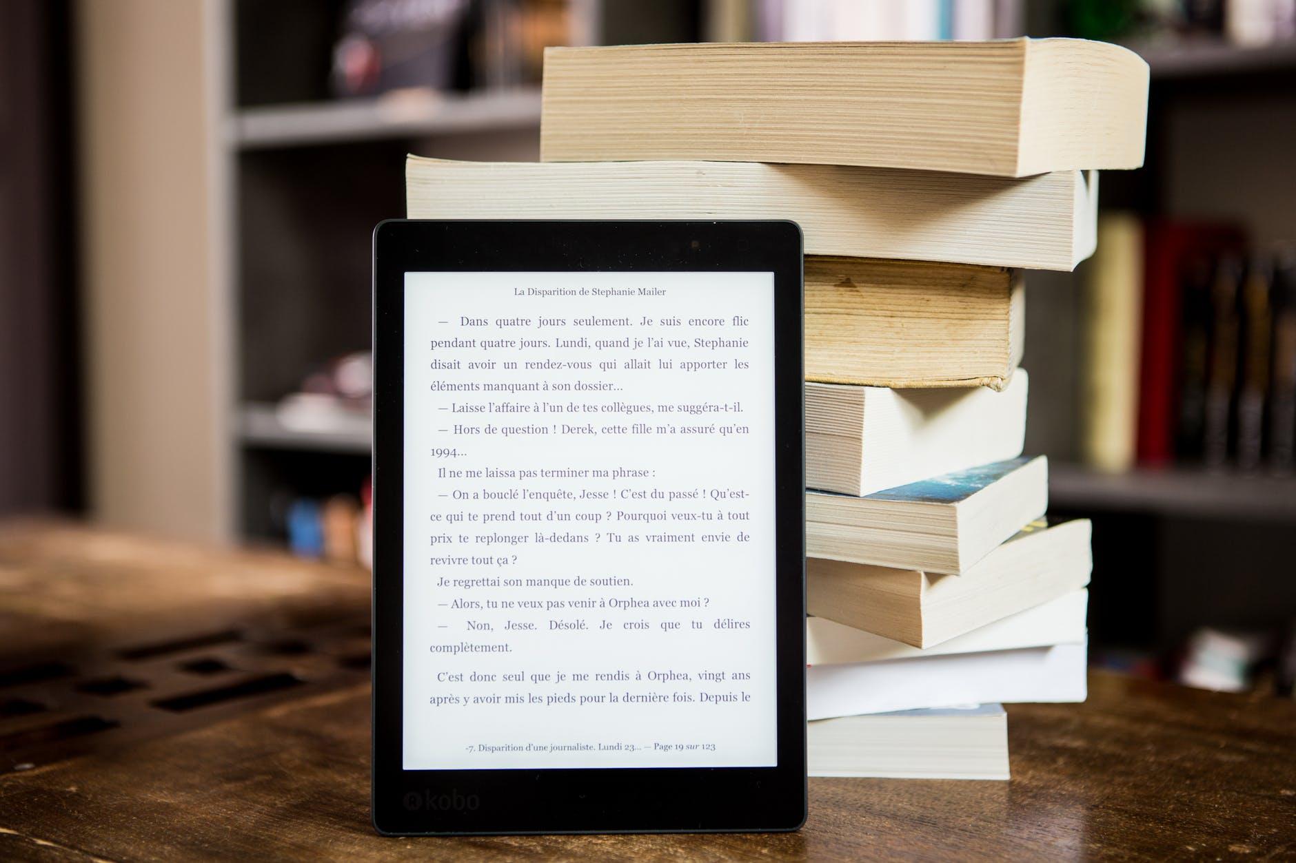 black tablet computer behind books